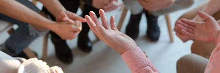 Panorama of therapist's hands while gesticulating during group therapy Stock Photo