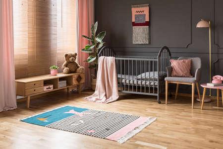 Echte foto van een babywieg staande tussen een lage kast en een fauteuil, lamp en kruk in het interieur van de kinderkamer met houten vloer en grijze muren met lijstwerk