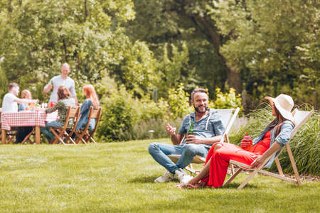 Smiling man with beer talking with friend while relaxing on sunbeds in the garden. Real photo