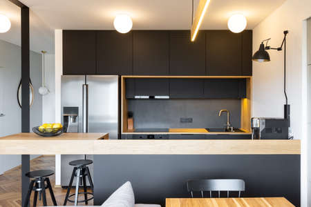 Black wooden furniture and an industrial lamp above a coffee machine in a beautiful, modern kitchen interior with dining space Foto de archivo