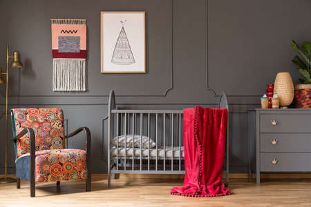 Real photo of a baby crib with a red blanket, an armchair, lamp and cupboard with ornaments in childs room interior Stockfoto