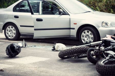 Car crash with a motorbike. Helmet and lights lying on the street