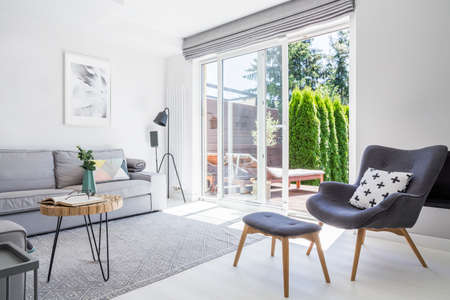 Fauteuil met gedessineerd kussen en kruk in het interieur van de woonkamer met grijze bank en posters. Echte foto
