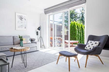 Sessel mit gemustertem Kissen und Hocker im Wohnzimmer mit grauem Sofa und Postern. Echtes Foto