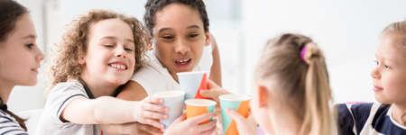 Grupo de niños felices bebiendo jugo de vasos de papel y divirtiéndose durante la celebración del día del niño Foto de archivo