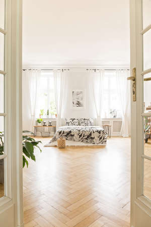 Loft bedroom interior with a herringbone parquet, bed, windows and plant. View through the door
