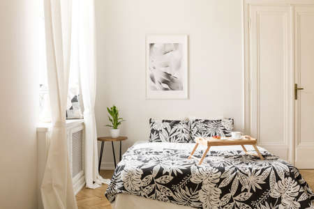 Real photo of a double bed with patterned sheets and wooden breakfast tray in a white bedroom interior Stock Photo
