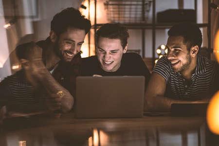 Amici felici che guardano film sul computer portatile durante la riunione sabato sera a casa
