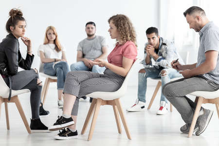 Young woman resolving problem with rebellious friend during group therapy with counselor Stok Fotoğraf