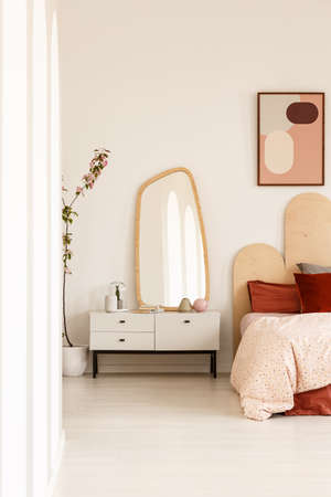 Mirror on white cabinet next to bed with headboard under poster in bright bedroom interior. Real photo