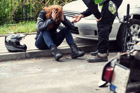Shocked biker holding her head and sitting on a pavement. Car driver trying to help Editorial