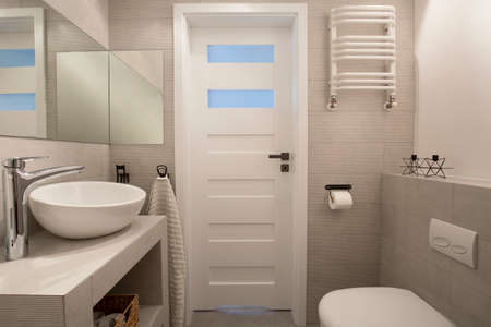 Mirror above washbasin in beige bathroom interior with toilet and door. Real photo Stock Photo