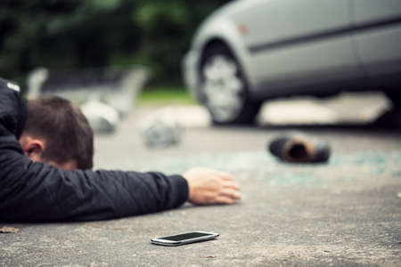 Dead pedestrian lying on the street next to his phone. Shoe, broken glass and car blurred in the background Stock Photo