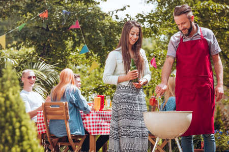 Smiling girl with beer next to friend and grill during birthday party in the garden Stock Photo