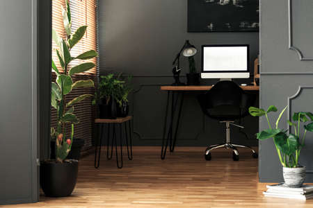 Mockup on desktop computer next to lamp in grey freelancers room interior with plants. Real photo
