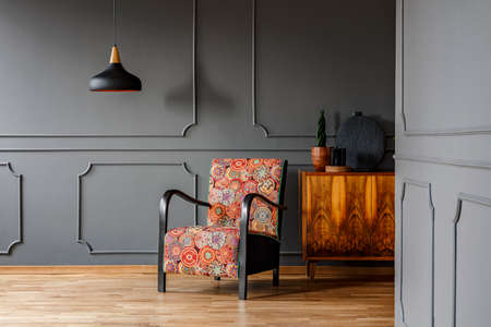 Patterned armchair next to wooden cabinet in grey living room interior with black lamp. Real photo