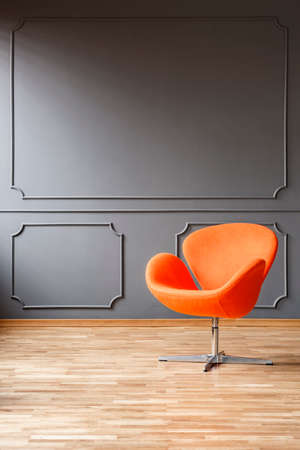 Modern orange armchair in minimal grey living room interior with wooden floor. Real photo with a place for your furniture Stock Photo
