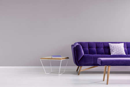 Pillow on a stylish, vibrant purple settee and a diamond shape, side table in a gray living room interior with place for a floor lamp. Real photo.