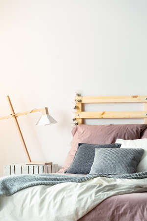 Grey pillows on pink bed with wooden headboard in white bedroom interior with lamp. Real photo Archivio Fotografico - 105811258