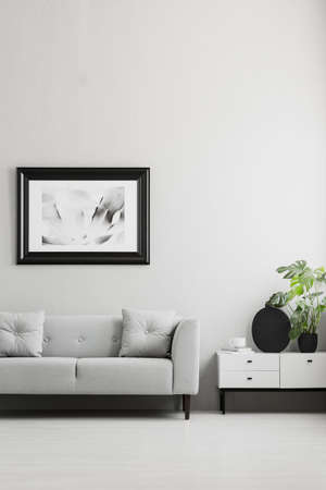 Photo in a black, thick frame on a gray wall, white sideboard and a comfy sofa in a stylish living room interior with place for a coffee table. Real photo. 写真素材