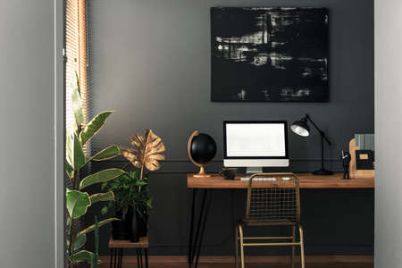 Painting above desk with desktop computer and lamp in grey and gold workspace interior. Real photo