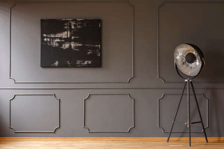 Black painting on grey wall with molding in dark apartment interior with lamp. Real photo. Paste your sofa here
