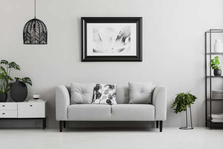 Black industrial bookcase and a plant stand next to an upholstered sofa in a gray living room interior with place for a coffee table. Real photo Stock Photo