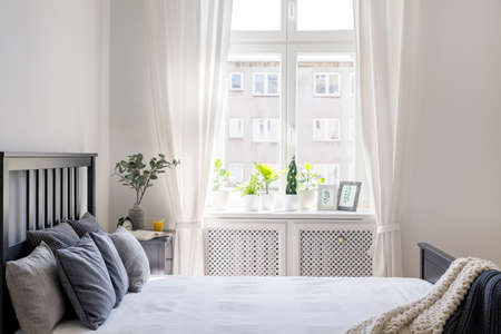 Knit blanket and pillows on bed in white hotel bedroom interior with drapes at window. Real photo Stock Photo