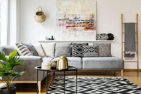 Gemusterte Kissen auf grauem Ecksofa im Wohnzimmerinnenraum mit Tisch und Malerei. Echtes Foto