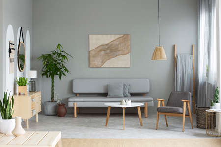 Real photo of grey sitting room interior with modern poster, lounge with cushions, armchair by wooden coffee table and straw lamp