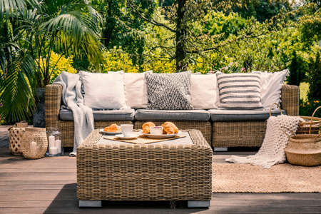 Close-up of a rattan outdoor table with coffee and croissants on it in front of a cozy sofa with white pillows on the patio of a spa hotel