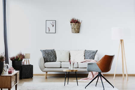 Grey armchair near couch with cushions in living room interior with poster and heather on white wall Фото со стока