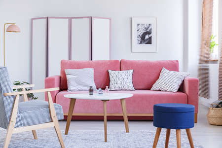 Blue stool next to wooden armchair in pastel living room interior with table and pink couch. Real photo