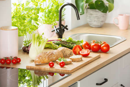 Herbs, bread and tomatoes on a cutting board next to a sink in a kitchen interior Banque d'images - 105924269