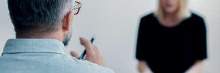 Gros plan sur le dos d'un psychothérapeute d'âge moyen tenant un stylo et la silhouette d'une patiente floue face à lui