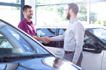Happy buyer of new car shaking hands with dealer after transaction in the salon
