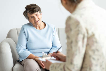Excited grandmother talking to a psychologist about positive life of pensioner Stockfoto