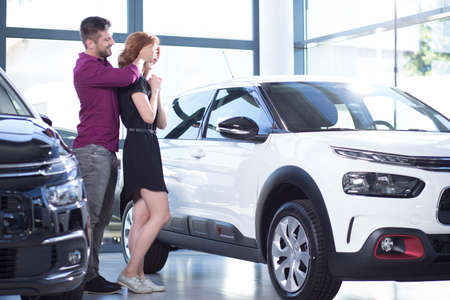 Man making a surprise for the wife in exclusive car showroom with luxury vehicles