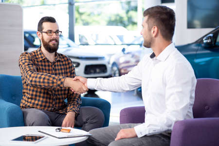 Professional car dealer shaking hands with buyer after transaction in the showroom