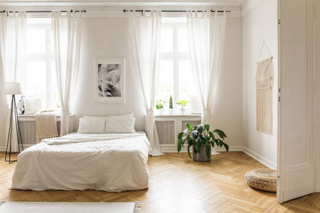 Poster between windows in bright bedroom interior with bed between plant and lamp. Real photo Foto de archivo - 105924335