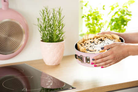 Close-up of girls hands holding a baking form with a cake above a countertop in a kitchen