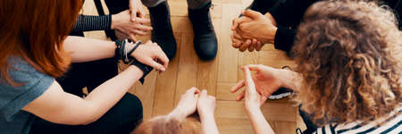 High angle view of hands of people in group therapy, talking and supporting each other Stock Photo