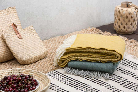 Blankets and rattan bags on table with cherries on the terrace of house. Real photo Banco de Imagens