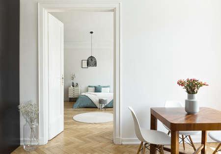 Flores en mesa de madera en interior plano blanco con lámpara sobre cama en dormitorio con alfombra. Foto real Foto de archivo