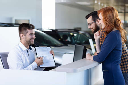 Smiling car dealer showing rental agreement to buyers in the showroom