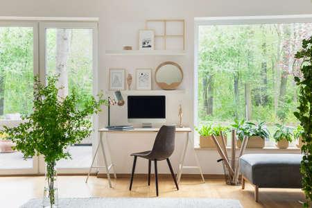Grauer Stuhl am Schreibtisch mit Desktop-Computer in scandi offenem Rauminnenraum mit Fenstern. Echtes Foto Standard-Bild