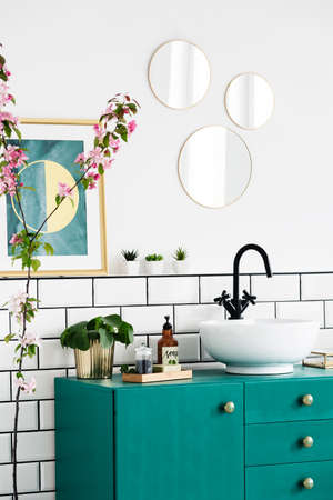 Mirrors and poster above green cabinet in modern bathroom interior with plants. Real photo Imagens