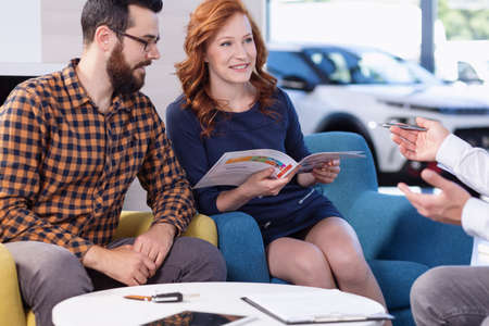 Smiling couple watching brochure in car showroom while talking with dealer