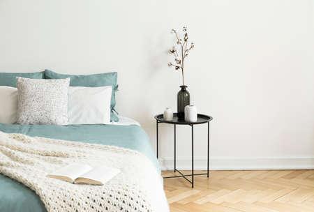 Zwarte tafel naast bed met groene lakens, kussens en gebreide deken in wit slaapkamer interieur. Echte foto met een plekje voor je fauteuil
