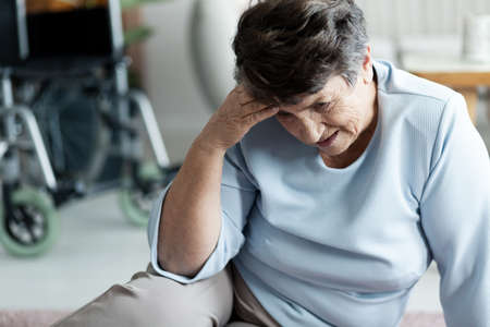 Grandmother with headache after falling on the floor in the nursing house Foto de archivo - 105920333